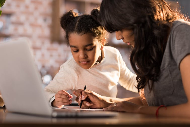 A woman and child working in front of a laptop