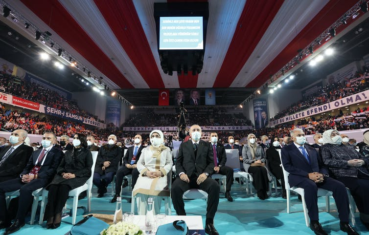 Turkish president Recep Tayyip Erdoğan and his wife Emine sitting wearing masks in the middle of a conference hall with a desk in the foreground.