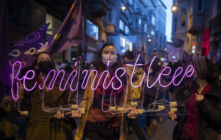 Women protesters carring a feminism neon sign and flags.