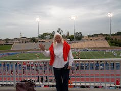 An elder woman in pigtails waves at the camera, standing in front of a sports field.