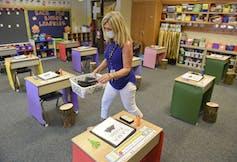 A first grade teacher wearing a mask puts materials on her students' desks.
