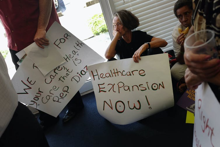 Protesters carrying signs that call for Medicaid expansion.