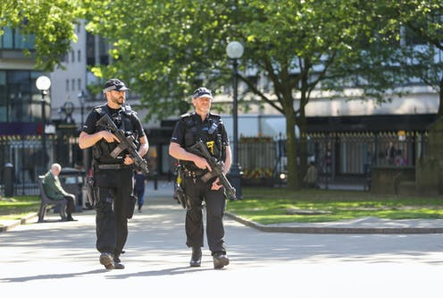 Two police officers carrying guns in park