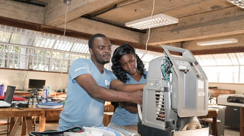 A man and a woman in a design studio reach into the back of a piece of medical equipment