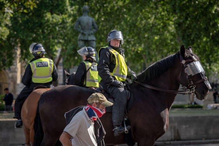 La police à cheval avec des casques alors qu'un passant masqué en casquette de l'armée passe