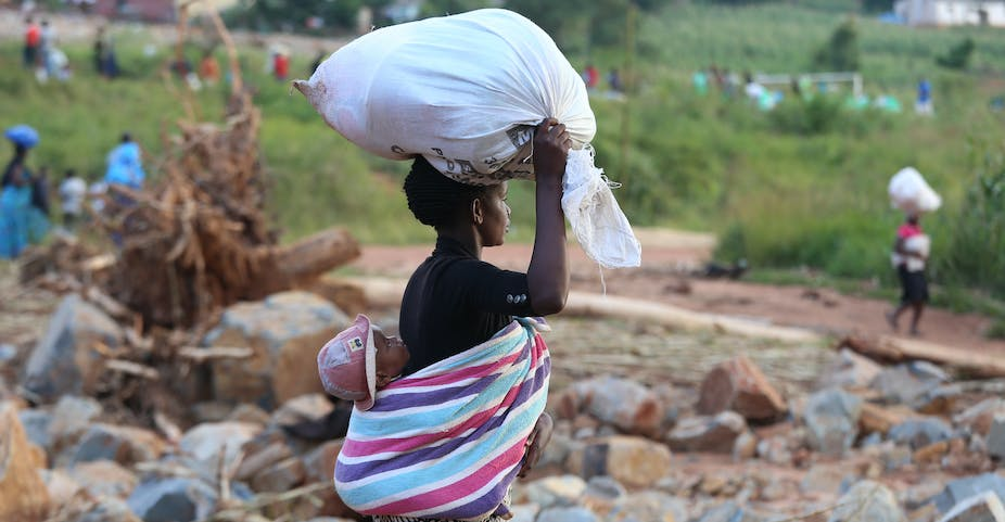 Woman carries a white sack on her head and a baby on the back, wrapped in a blanket.