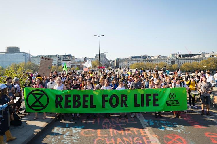 Les manifestants traversent le pont en tenant un grand panneau vert avec le logo Rebellion Extinction et les mots