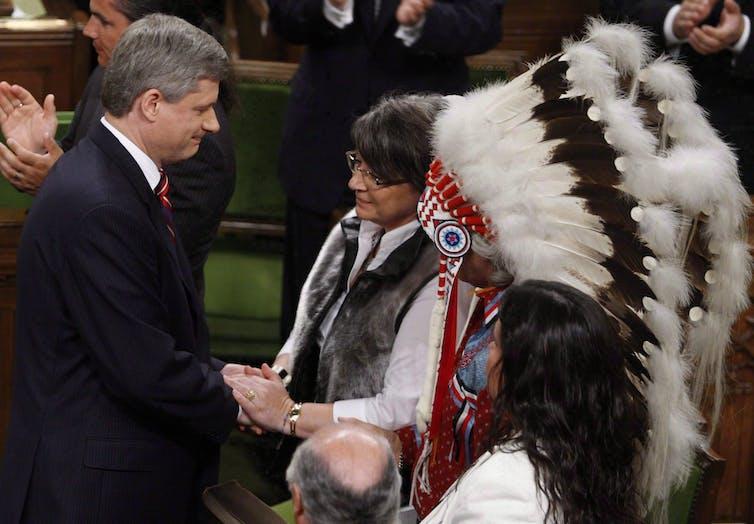 Former prime minister Stephen Harper shakes hands with former Inuit Tapiriit Kanatami president Mary Simon