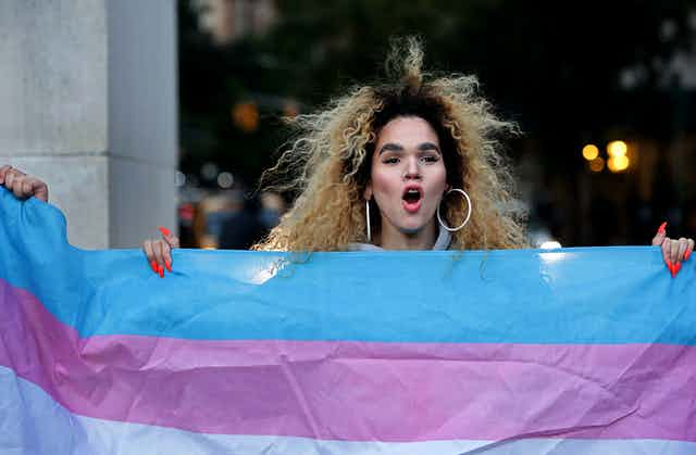 A trans woman holds a transgender pride flag
