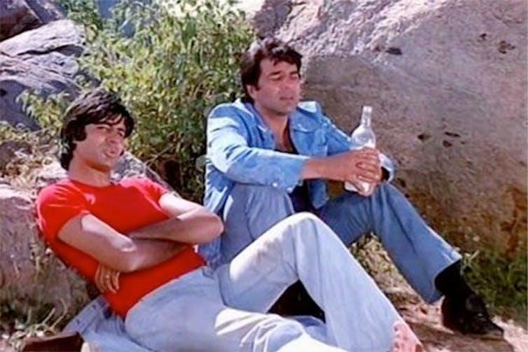 Two men lean against a rock. Both wear jeans.