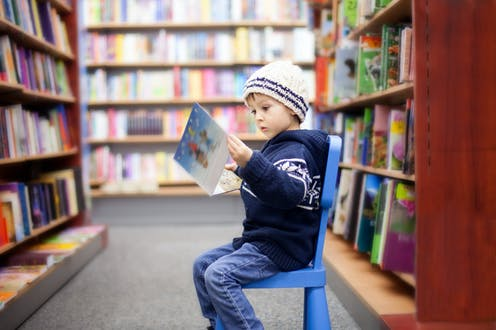boy seated in library reading a book