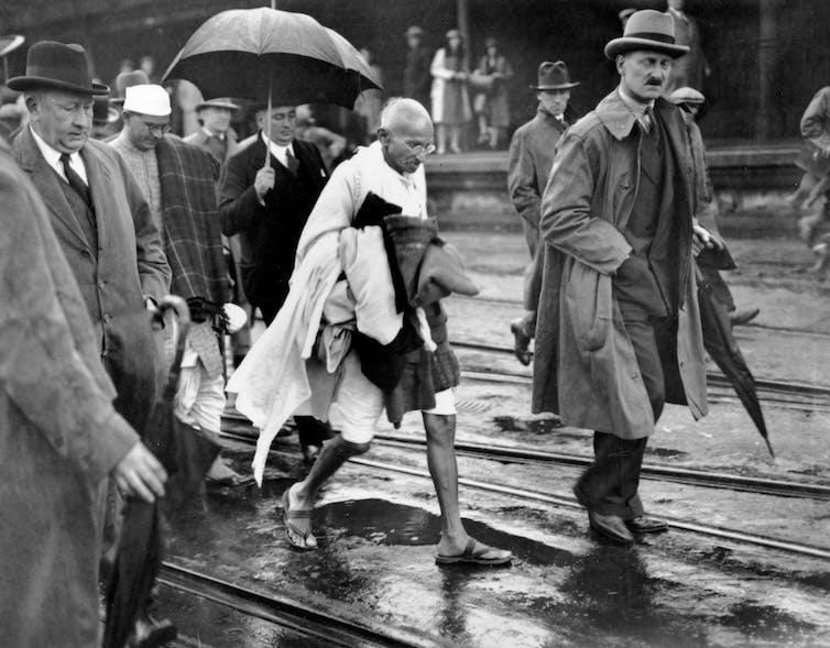 Gandhi walks in his dohti next to men in suits.