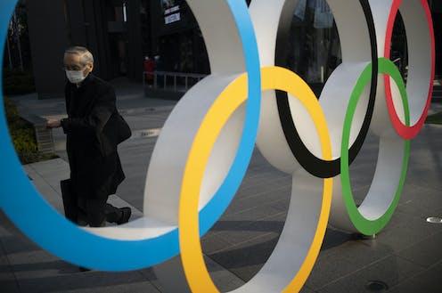 Man wearing mask walks behind Olympic rings