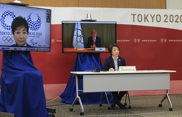 International Olympic Committee president Thomas Bach (virtually) delivers an opening speech while Tokyo 2020 Organizing Committee president Seiko Hashimoto and Tokyo Governor Yuriko Koike (virtually) listen.
