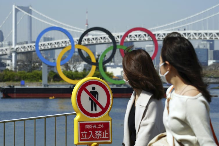 Two Japanese women wearing masks walk by Olympic rings and a no-trespassing photo