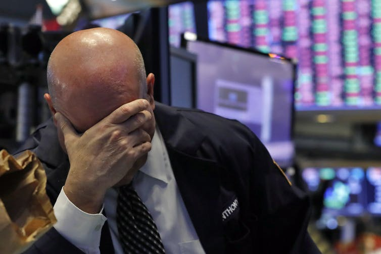 A stock trader presses his hand to his head on the floor of the New York Stock Exchange.