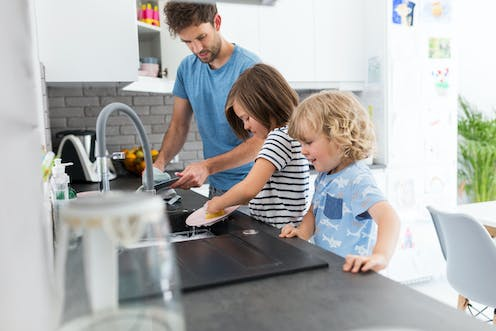 Father washing dishes with children.