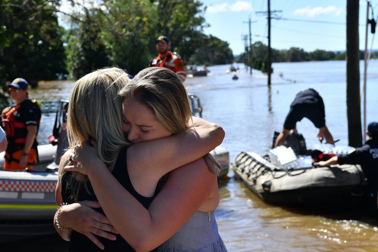 Mother and daughter hugging in foreground of floodwaters