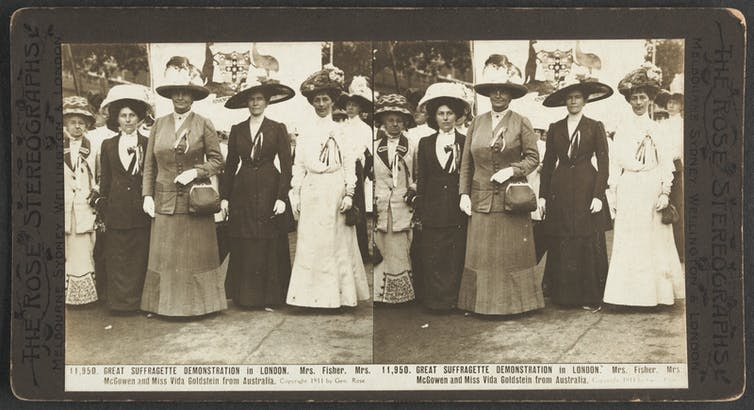 Five women, whole-length, full face, wearing full length gowns, jackets, wide brimmed decorated hats, standing in a row. Text reads: Mrs. Fisher, Mrs. McGowen and Miss Vida Goldstein from Australia.