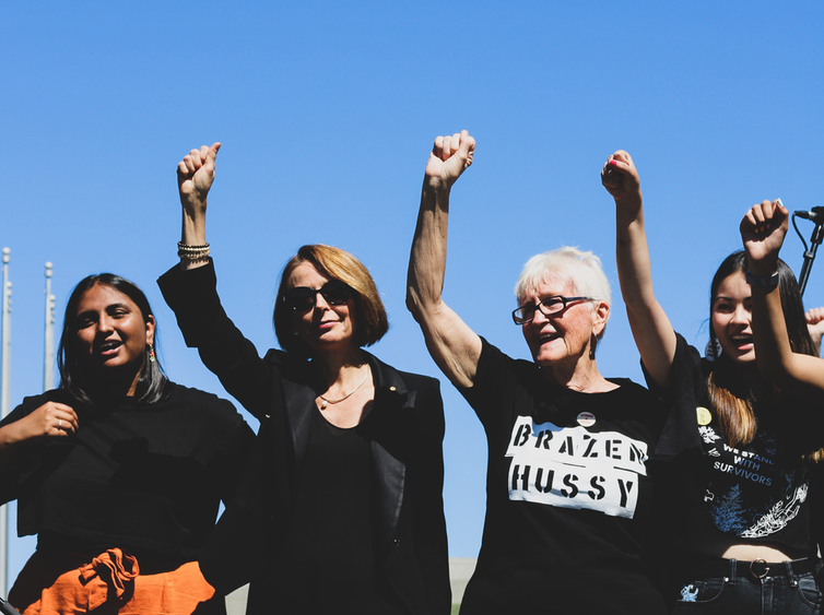 Four women of different ages stand with a fist in the air.