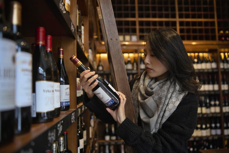 A woman holds a bottle of wine in a bottle shop in China