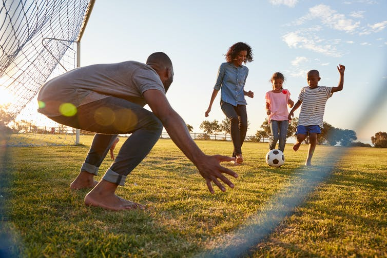 Father and children playing football together