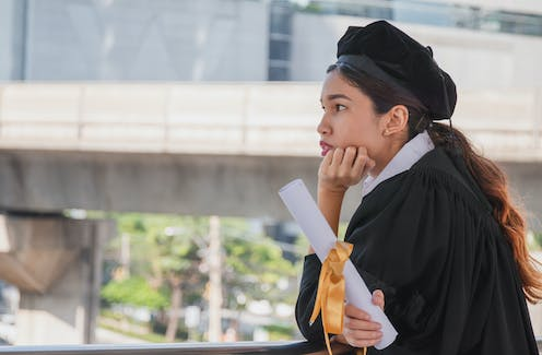 Young female graduate holding degree certificate and looking pensive