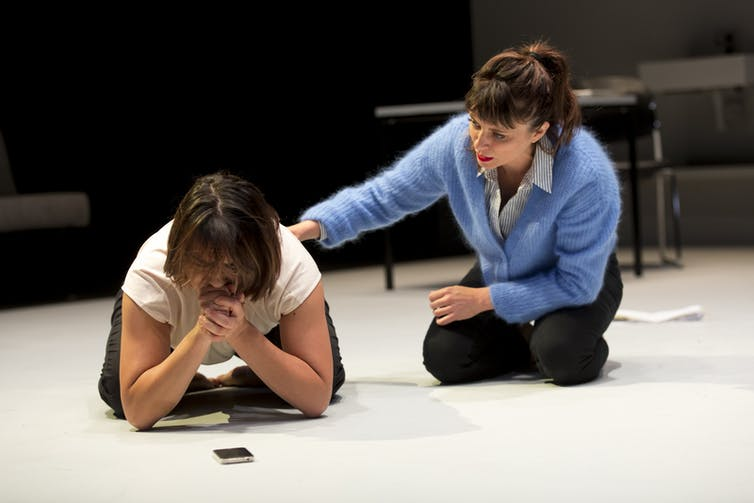 A woman kneels on the ground and cries, comforted by a friend.