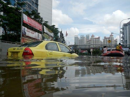 Taksi berwarna kuning tenggelam oleh banjir dengan gedung sebagai latar belakang.