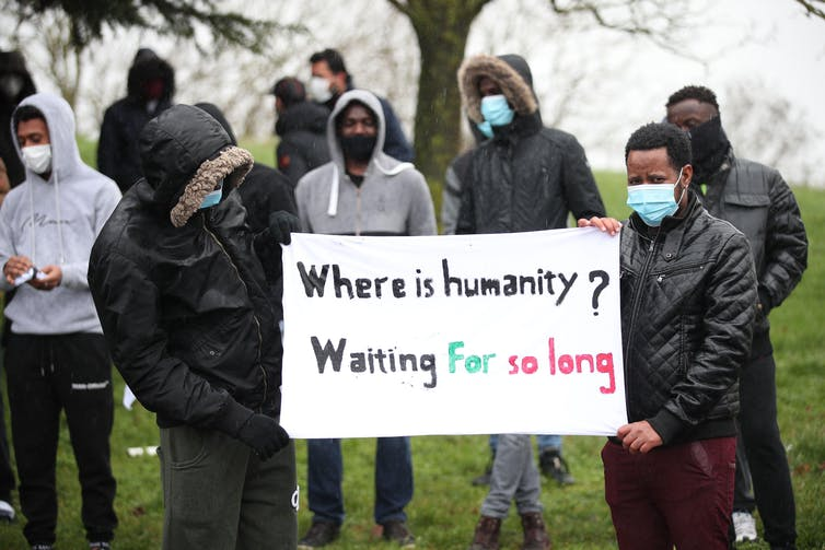 Protesters with face masks and black and grey jackets hold sign reading 'Where is humanity? Waiting for so long'