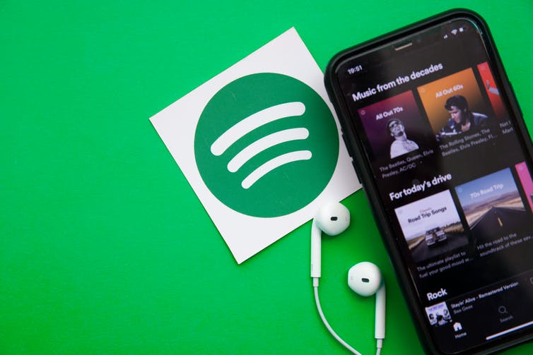 A phone showing Spotify playlists against a green blackground