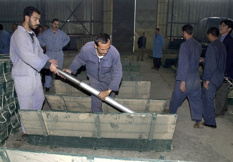 Two Iraqi workers put a missile in a box at the Dhu-Alfhiqar factory, December 2002 during a visit to the Nasr military industries complex in al-Taji, 50kms north-west of Baghdad, by UN arms experts.