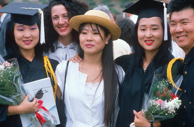 Two Asian American women in graduation gowns pose with other people