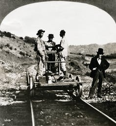 Three Asian-American men stand on a railroad pushcart