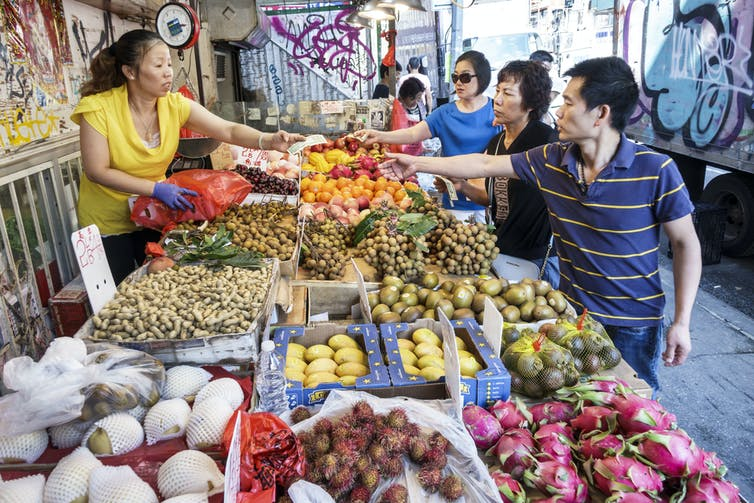 Asian woman hands change back to three Asian American customers, over a large outdoor fruit display