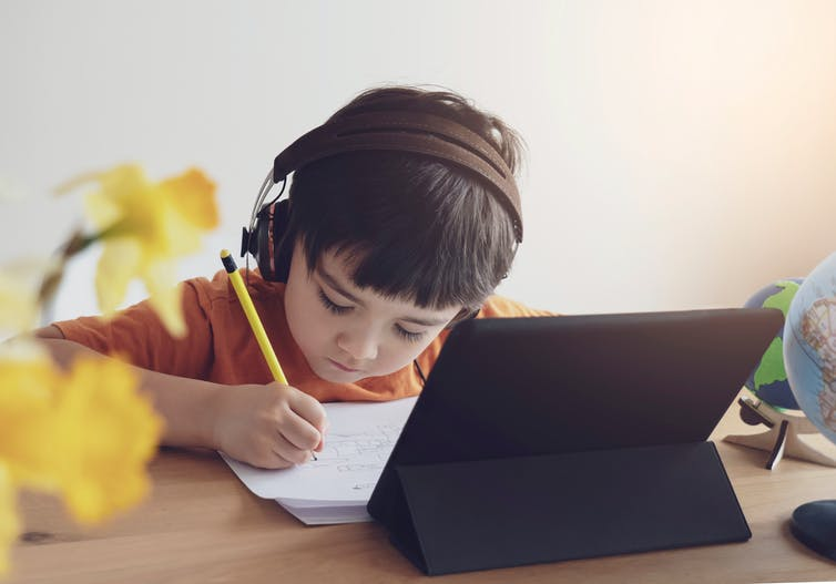 A child doing school work at home with a tablet