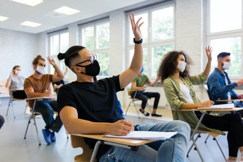 A group of masked college students raise their hands in class.