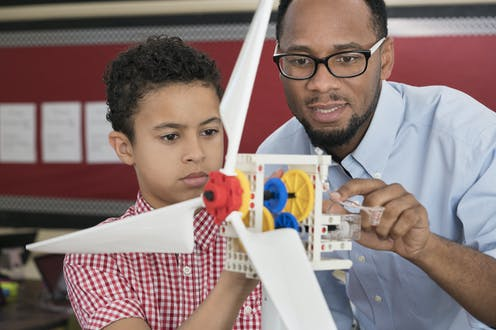 An African American students and his science teacher use a model wind turbine together in class.