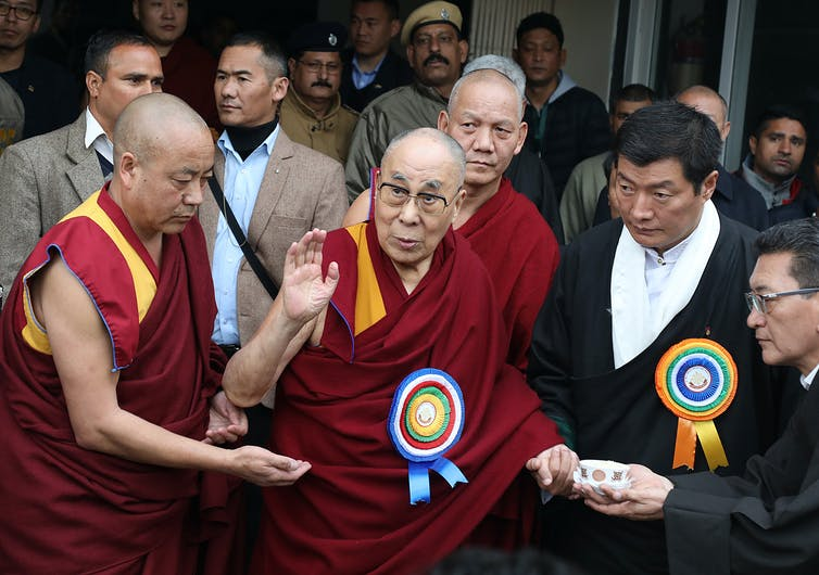 Tibetan spiritual leader Dalai Lama, surrounded by Buddhist monks and supporters, greets spectators.
