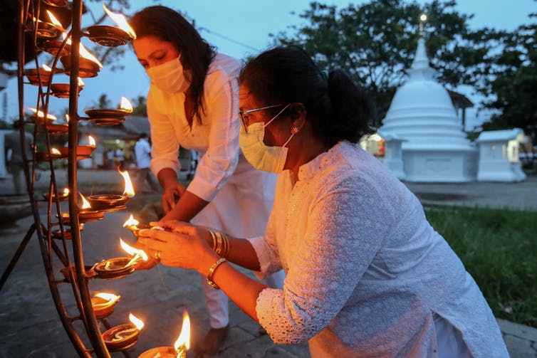 Two women dressed in white and wearing face masks light candles at a Buddhist shrine in Colombo, Sri Lanka.