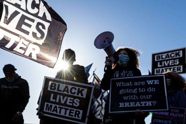 Protesters hold 'Black Lives Matter' signs.