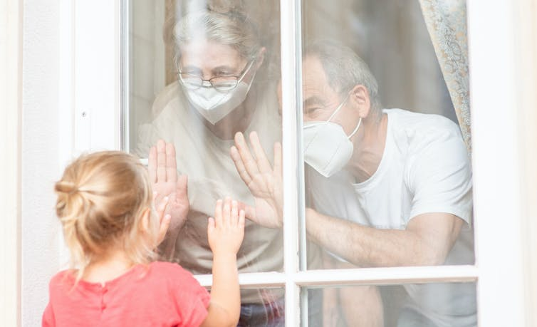 Grandparents with masks seen pressing hands against window looking at granddaughter