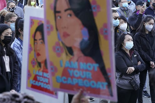 """A poster that says """"I am not your Scapegoat"""" is held up at a protest."""