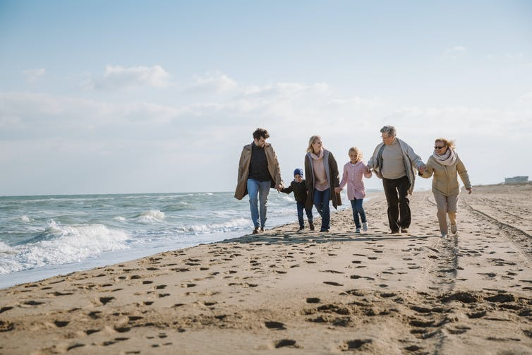 Multigenerational family, walking, holding hands on the beach.