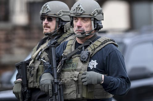 Two police officers wearing protective gear and looking sad.