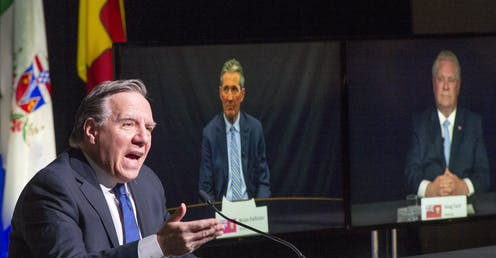 QuébecFrancois Legault speaks as Brian Pallister and Doug Ford appear on video screens behind him.