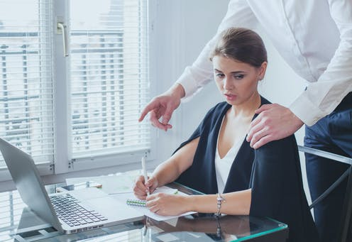 A woman sits as a desk with an uncomfortable look as a man standing behind puts his left hand on her left shoulder