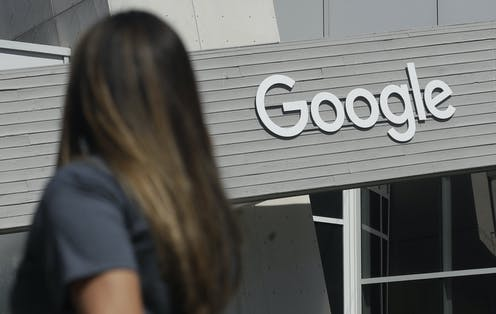 A woman is seen from behind as she walks past a building with a large Google sign.