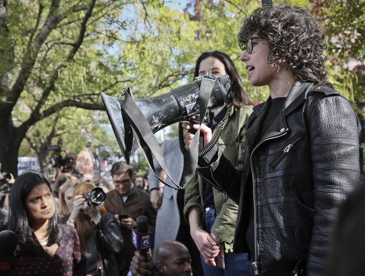 A woman with curly hair speaks into a megaphone.