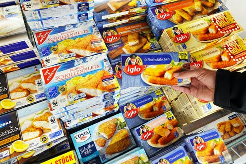 A hand holding a pack of fish fingers in a supermarket freezer aisle.